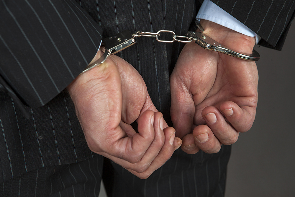Businessperson in handcuffs